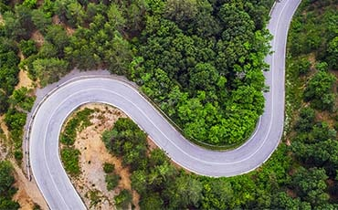 Flygfoto på slingrig väg i grön skog